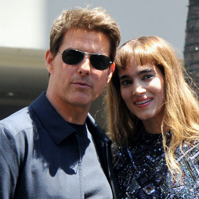 Tom Cruise in a blue shirt and jacket with Sofia Boutella in a black dress