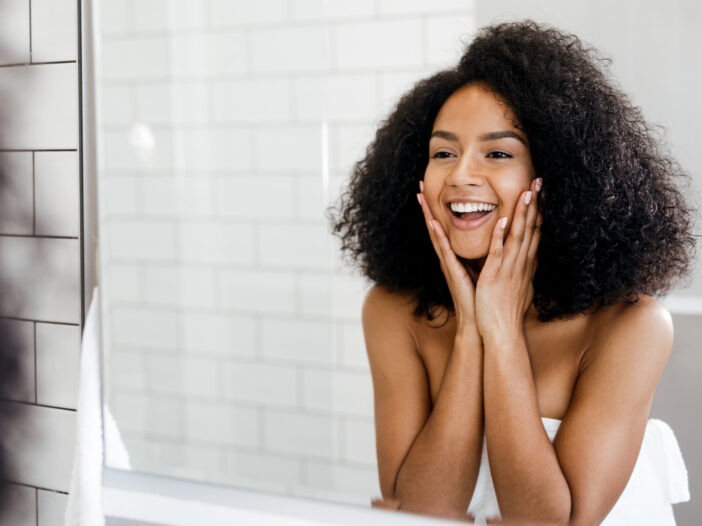 Image of woman smiling in the mirror.