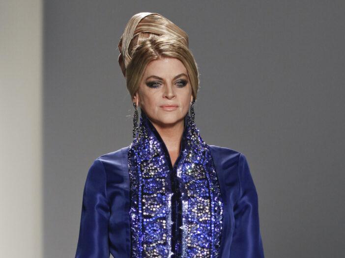 Kirstie Alley in a blue dress walking the runway