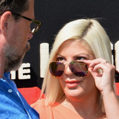 Tori Spelling pulls down her sunglasses to look at Dean McDermott on the red carpet