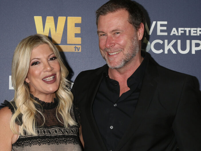 Tori Spelling standing with Dean McDermott, both laughing