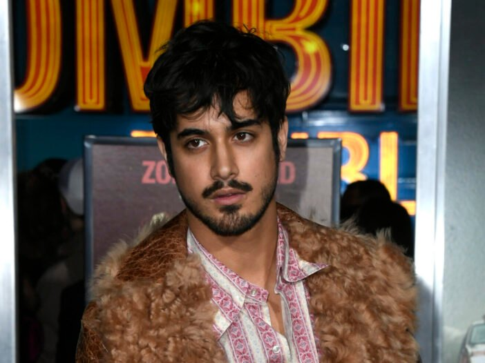 Avan Jogia wearing a brown vintage jacket and pink and white striped button down at the Zombieland 2: Double Tap premiere in 2019