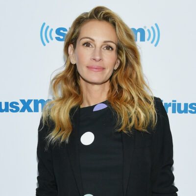 Julia Roberts in a black blouse in front of a white background