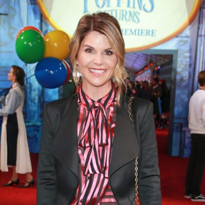 Lori Loughlin smiling in a grey jacket and red blouse