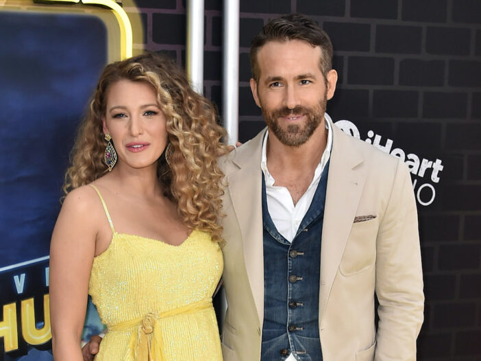 Blake Lively in a yellow dress with Ryan Reynolds in a khaki suit