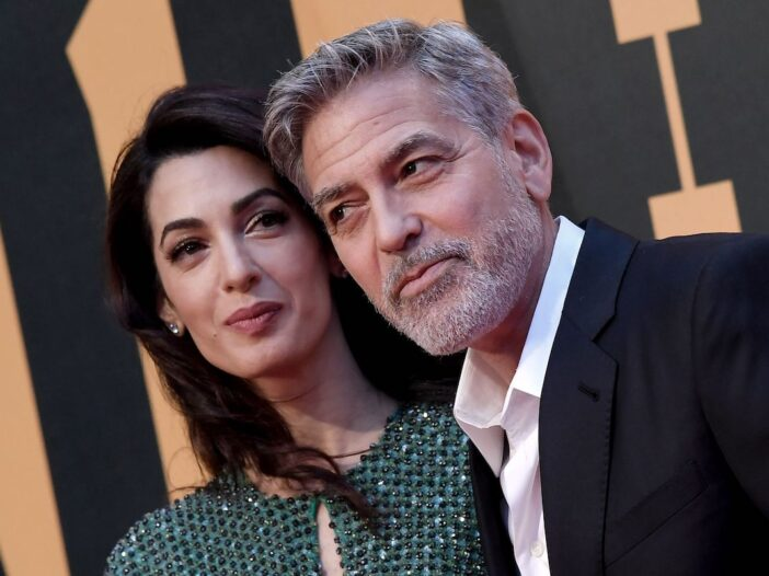 close up of George Clooney smiling at and eyeing Amal Clooney