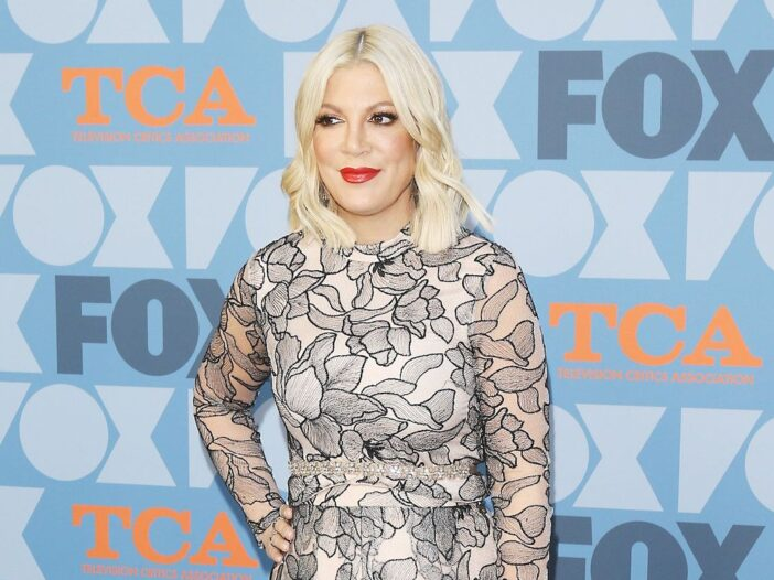 Tori Spelling with hand on hip in a white and black dress