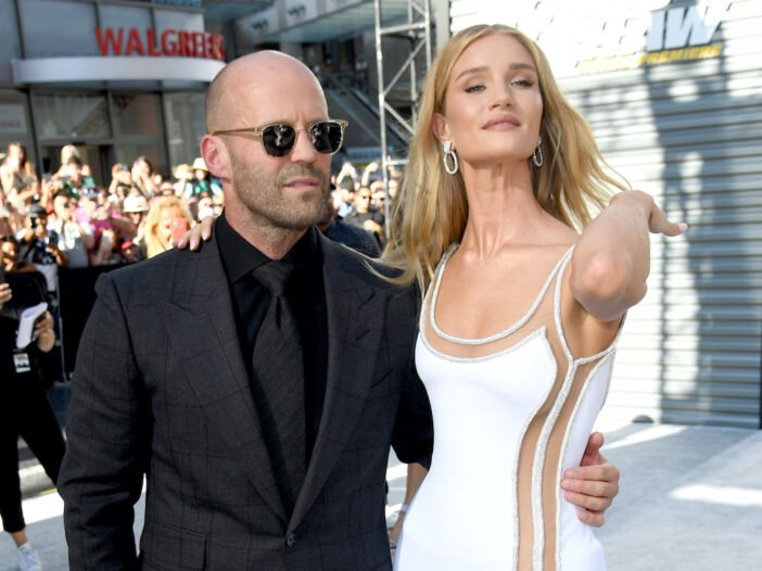 Jason Statham in a black suit with Rosie Huntington Whiteley in a white dress