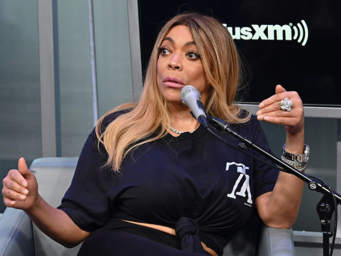 Wendy Williams sitting in a chair speaking into a microphone