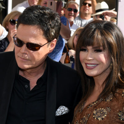 Donny Osmond in a black suit with Marie Osmond in a yellow dress