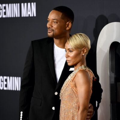 Will Smith in a black jacket with Jada Pinkett Smith in a peach dress