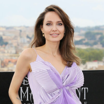 Angelina Jolie smiling in a purple top