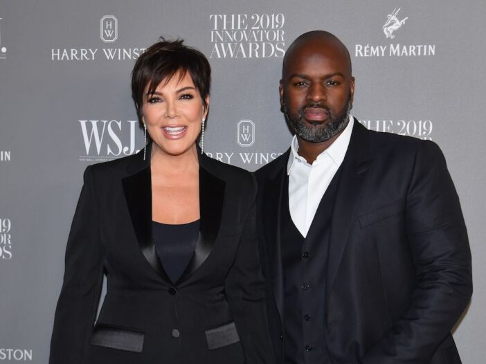 Kris Jenner in a black blouse and jacket with Corey Gamble in a charcoal suit
