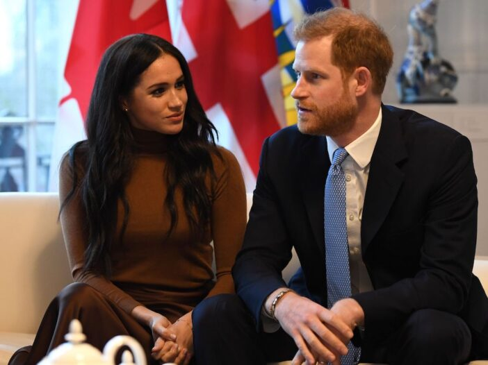 Meghan Markle in a brown sweater with Prince Harry in a navy suit