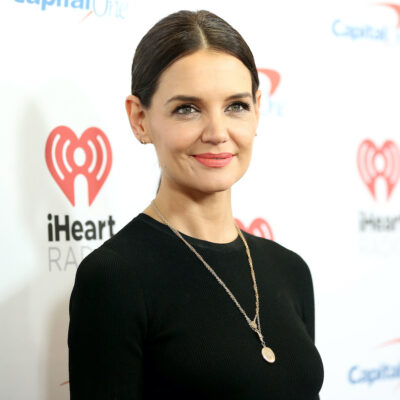 Katie Holmes smiling in a black blouse
