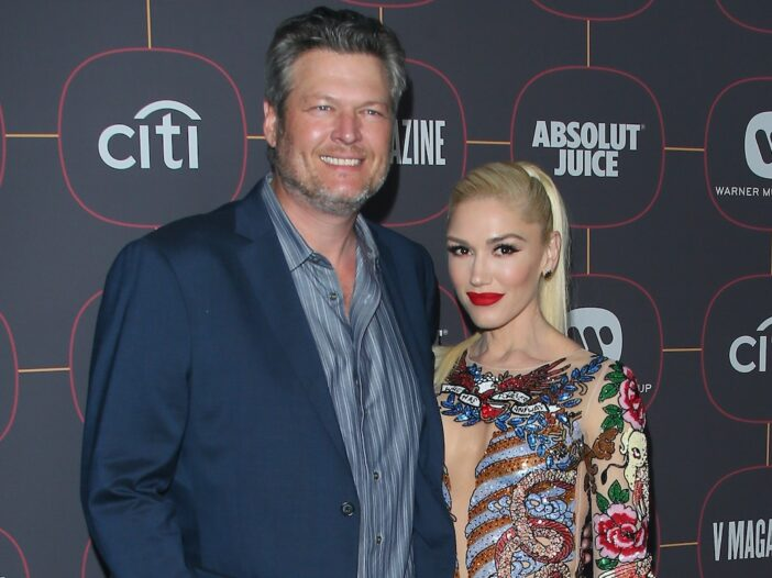 Blake Shelton in a suit with Gwen Stefani in colorful dress