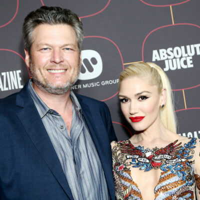 Blake Shelton in a blue suit with Gwen Stefani in a multicolored dress