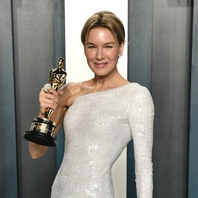 Renee Zellweger smiling in a white dress holding her oscar