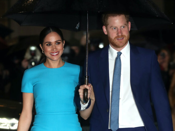 Meghan Markle in a blue dress with Prince Harry in a blue suit holding an umbrella