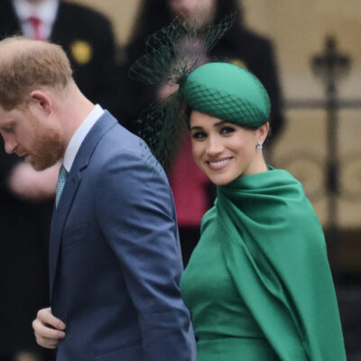 Meghan Markle smiling at the camera in green with Prince Harry in a blue suit