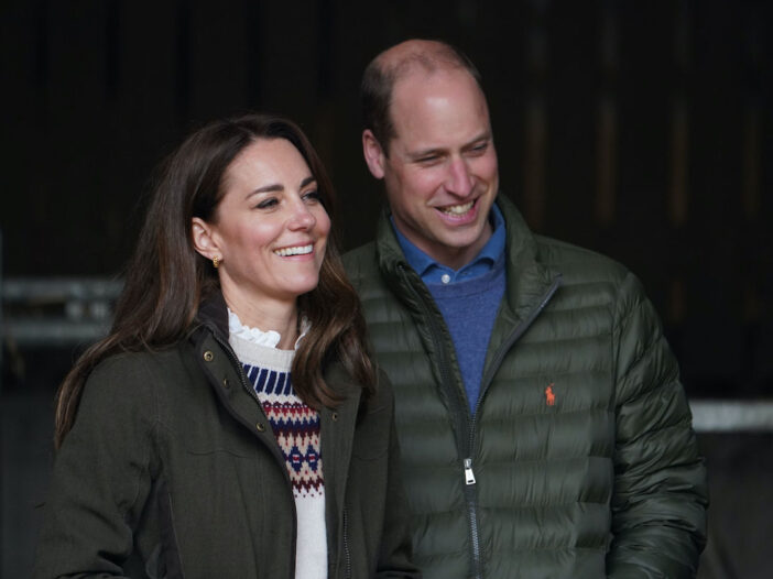 Kate Middleton in a green jacket smiling with Prince William in a puffy jacket