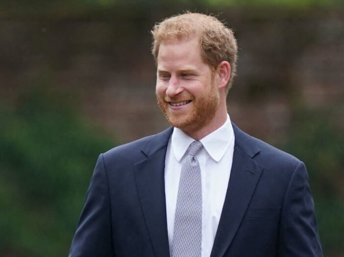 Prince Harry smiling in a blue coat outside