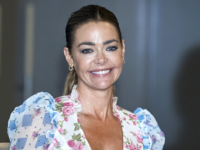 Denise Richards smiling in a white floral dress