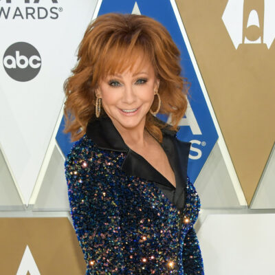 Reba McEntire smiling in a blue and gold dress