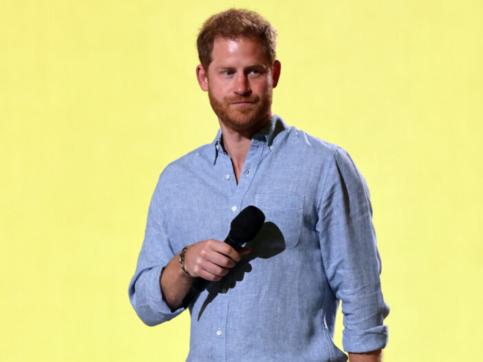 Prince Harry holding a microphone in a blue shirt