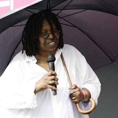Whoopi Goldberg in a white outfit holding an umbrella and microphone