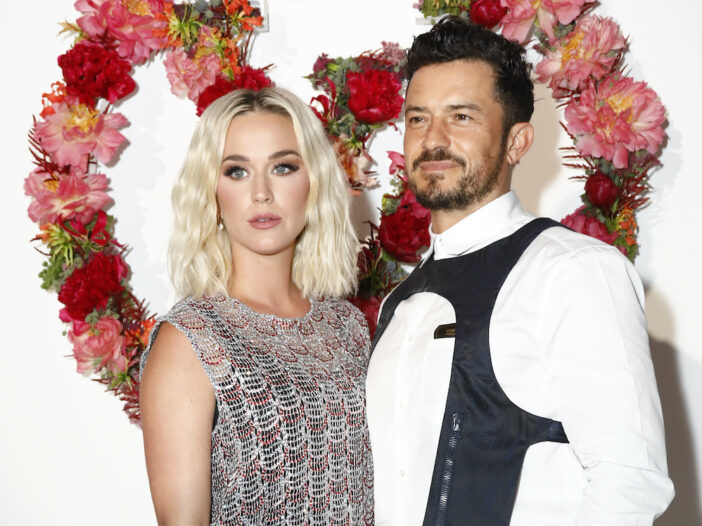Katy Perry in a grey dress with Orlando Bloom in a white shirt and black vest