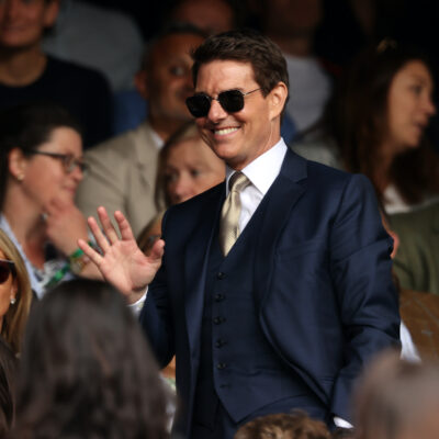 Tom Cruise in a suit smiling in a crowd