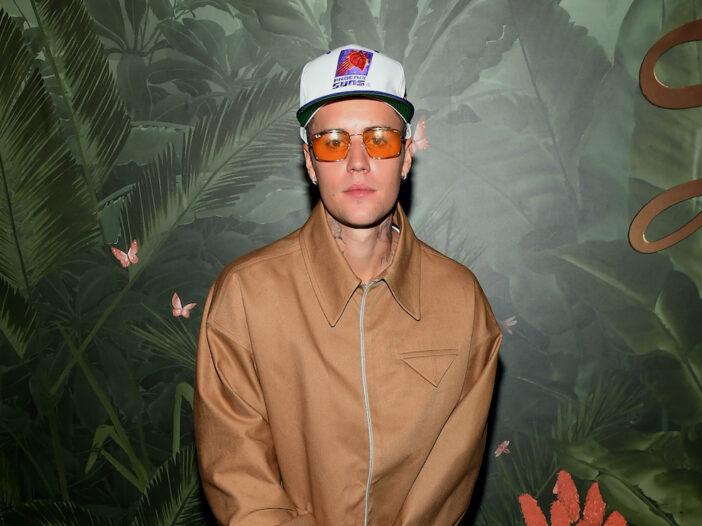 Justin Bieber in orange sunglasses, brown coat, and white hat