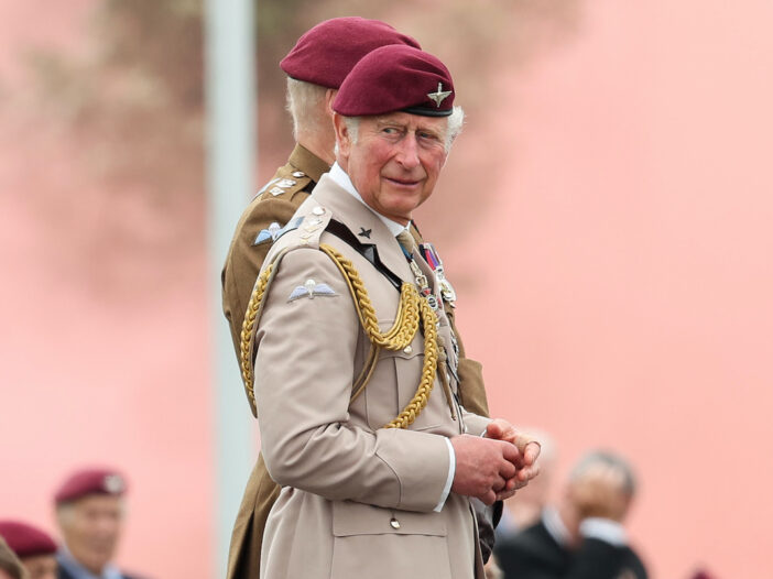 Prince Charles in a military outfit and red beret looking over his shoulder