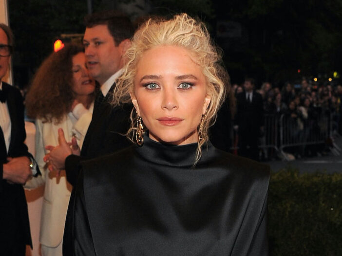 Mary Kate Olsen with platinum blonde hair in a black dress in 2012