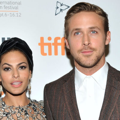 Eva Mendes in a silver dress with Ryan Gosling in a brown suit