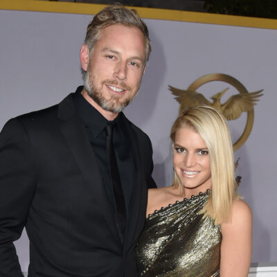 Eric Johnson in a black suit with Jessica Simpson in a gold dress
