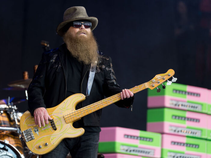 Dusty Hill playing bass on stage in a black outfit