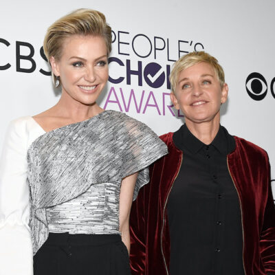 Ellen DeGeneres in a red jacket with Portia de Rossi in a white and black blouse
