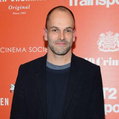 Jonny Lee Miller in a black jacket against an orange background