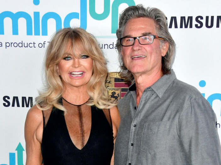 Goldie Hawn in a black dress with Kurt Russell in a grey shirt