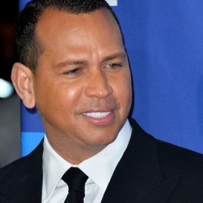 Alex Rodriguez holds up his phone to take a photo of an out of frame Jennifer Lopez on the red carpet
