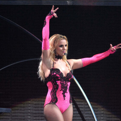 Britney Spears performing on stage with her arms up