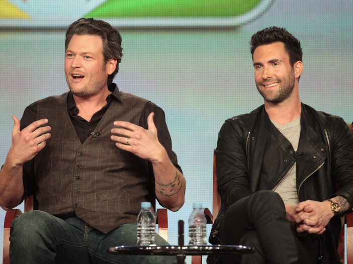 """Blake Shelton with a """"who me"""" look sitting next to Adam Levine"""