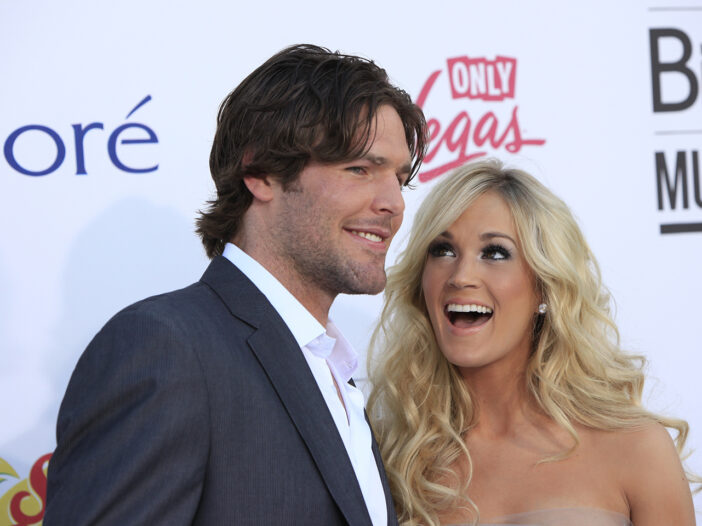 Carrie Underwood on the left, looking at laughing with Mike Fisher