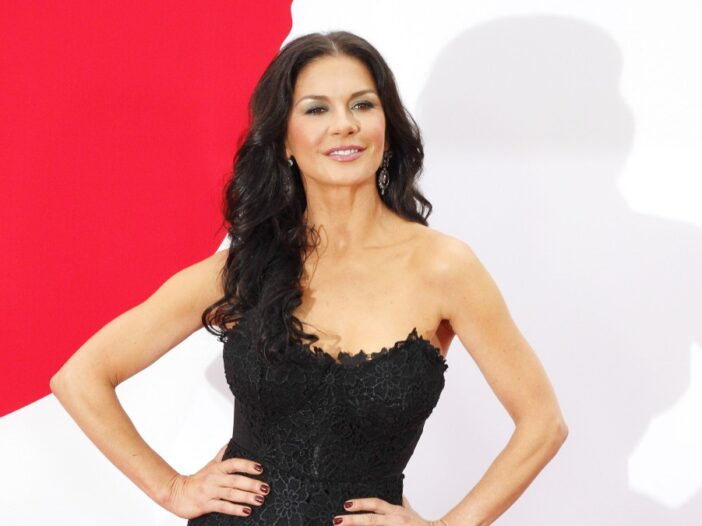 Catherine Zeta-Jones wears a black dress against a red and white background