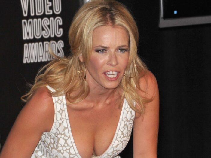 Chelsea Handler bends over while wearing a white dress at the MTV VMAs