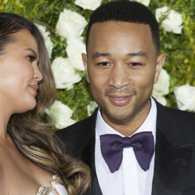 Chrissy Teigen looks at John Legend as both wear formal wear against a backdrop of flowers