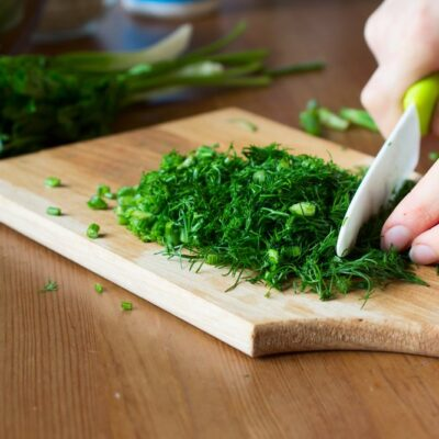 Cutting fresh herbs with a ceramic knife on wooden board. Cooking