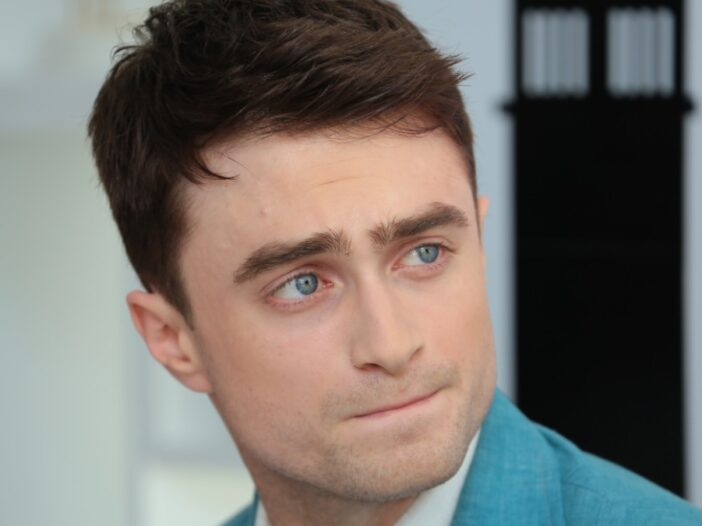 Daniel Radcliffe looks off to the side while wearing a blue suit that matches his dreamy eyes